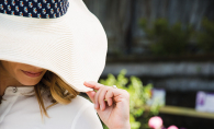 A woman dips the brim of her sun hat, protecting her eyes from UV damage.
