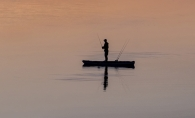 A person fishes from their boat at sunset on the lake.