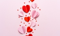 Paper hearts on a pink background.