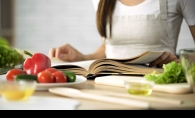 """A woman reads from """"Salt, Fat, Acid, Heat"""" while preparing a meal."""