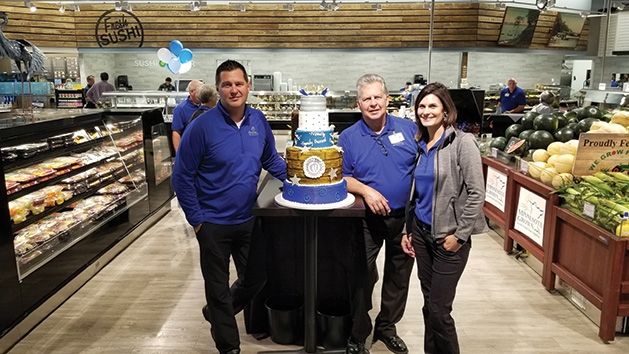 Employees pose with a cake at Mackenthun's Fine Foods Grand Opening
