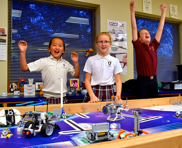 Three St. Hubert's students cheer as they watch their Hubots.