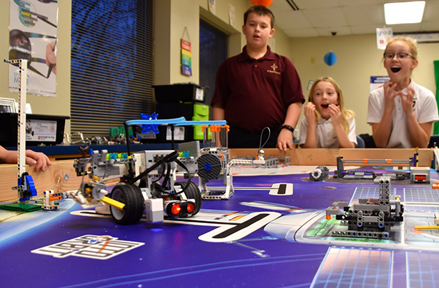 Three St. Hubert's students watch their Hubots in action.