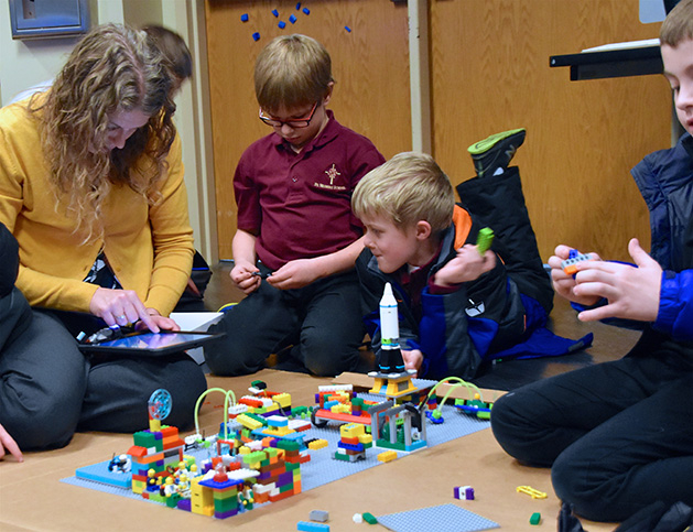 A parent coach works on a Hubot with St. Hubert's students.