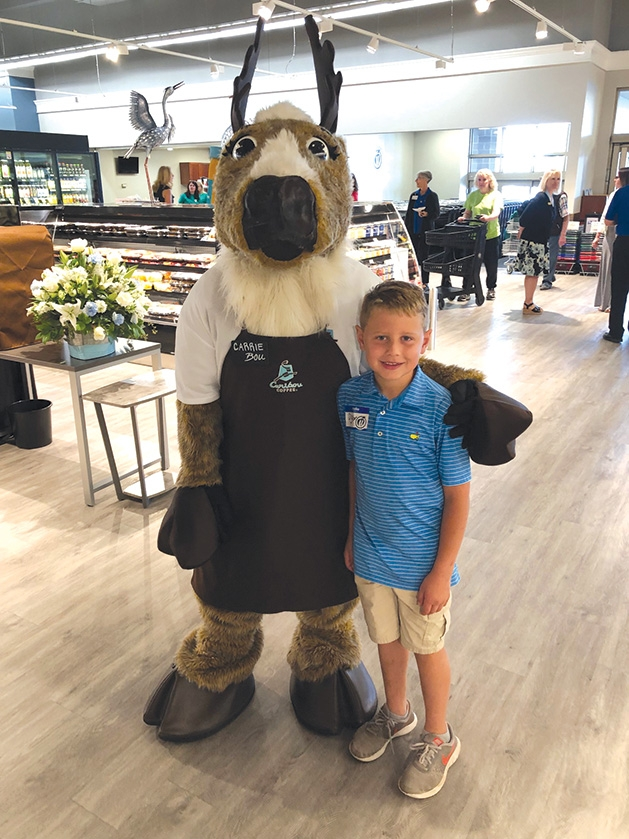A boy poses with a costumed mascot at Mackenthun's Fine Foods Grand Opening