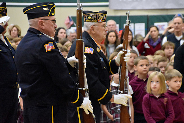 Two veterans hold their rifles as they are honored on Veteran's Day at St. Hubert's School.