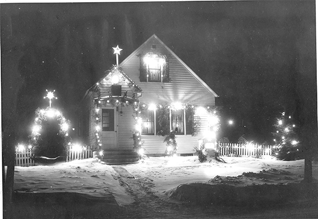 A black and white photo of a house decorated with Christmas lights.