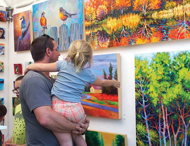 A man and his daughter look at some art at the Spirit of the St. Croix Art Festival.