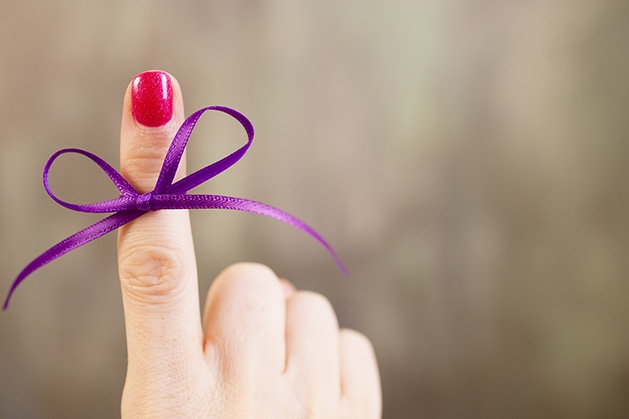 A purple ribbon tied around a finger, representing Alzheimer's Awareness Month.