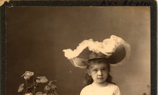 In this historical photo, a young girl wears an Easter bonnet