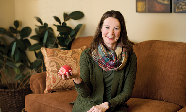 Lisa Domyahn, a certified holistic health and fitness coach who owns Solid at My Core, sits on a couch holding an apple.
