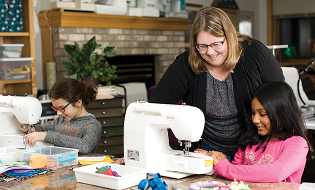 Judy Haning of Judy's Sewing School helps a student at a sewing machine.