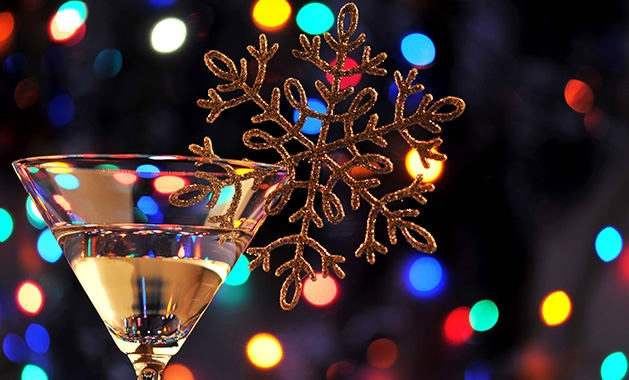 A martini with a snowflake decoration sits in front of Christmas lights.