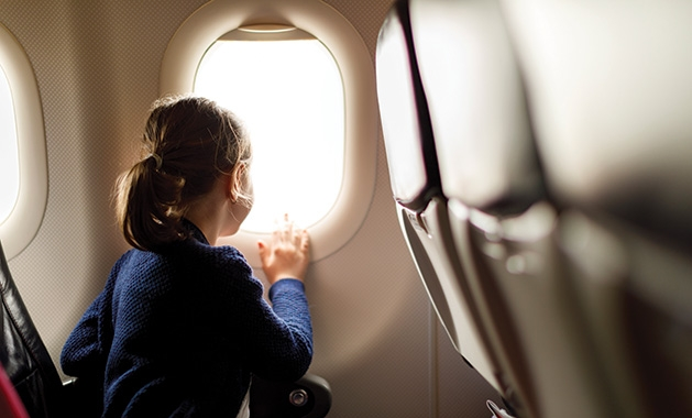 A child looks out the window of a plane.
