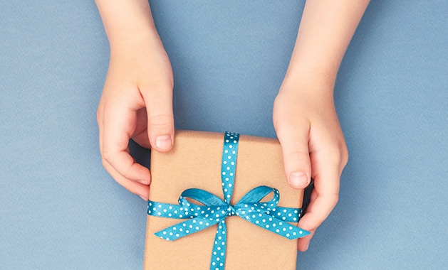 A person offers a gift wrapped in brown paper and tied with a blue ribbon.