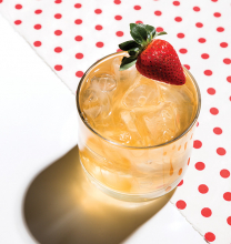 An amaretto gold cocktail garnished with a strawberry, made with a recipe from Dolce Vita Wine Shop.