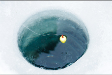 A bobber rests in an ice fishing hole carved into a lake.