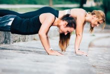 Two women plank in a park