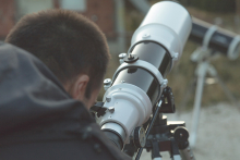 A man looks through a telescope on Astronomy Day.