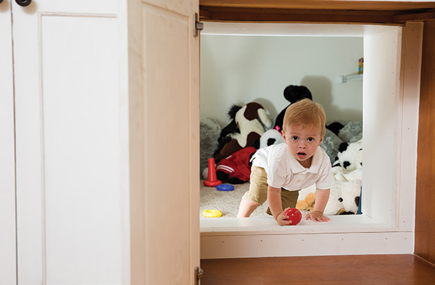 A young child stares out of a cupboard door in a remodeled Chanhassen home.